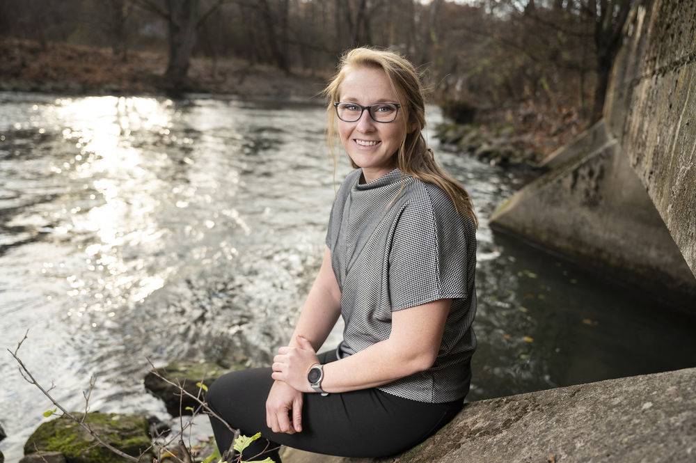 Rachel Schwaab smiling while sitting on a rock at the river's edge.
