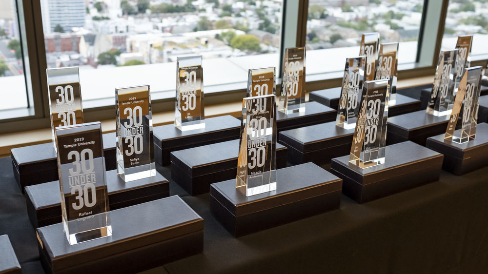 30 Under 30 awards from 2019 are displayed on a table in front of a window overlooking Philadelphia.