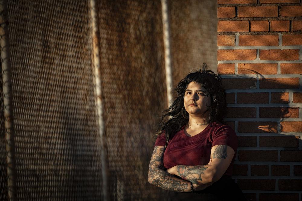 Noelia Rivera-Calderón leaning against a brick wall.