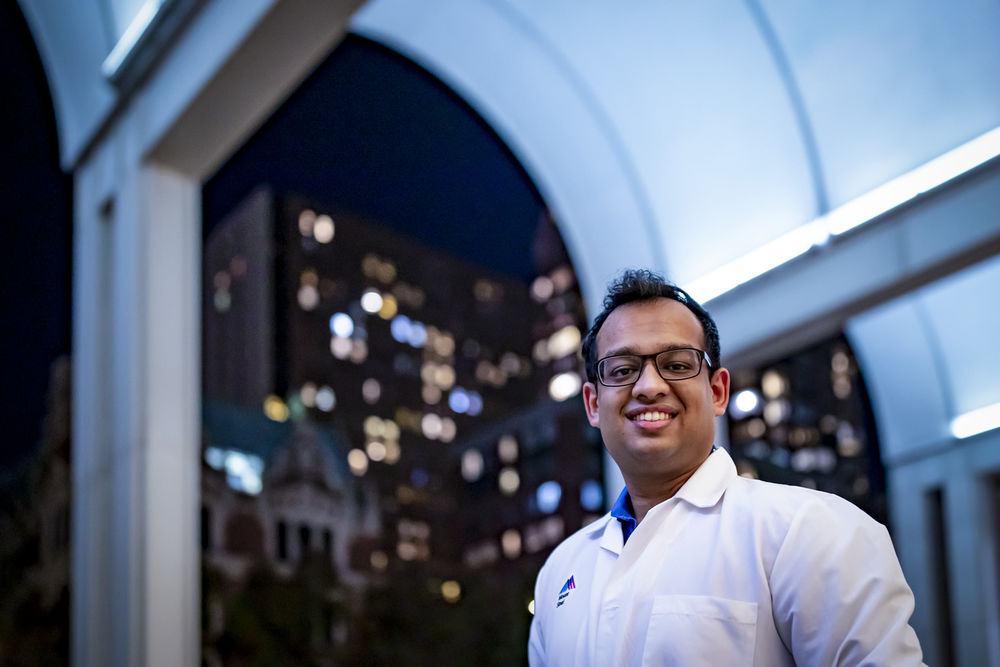 Keval Ray smiling while facing forward in front of a building at night.