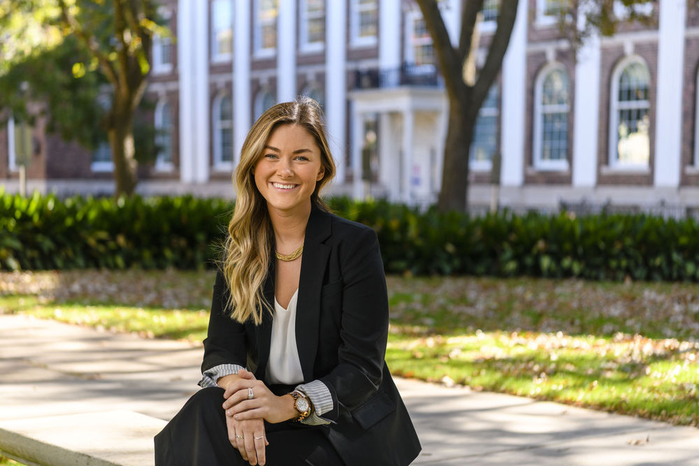 Brooke Williams sitting on a bench outside of an office building.